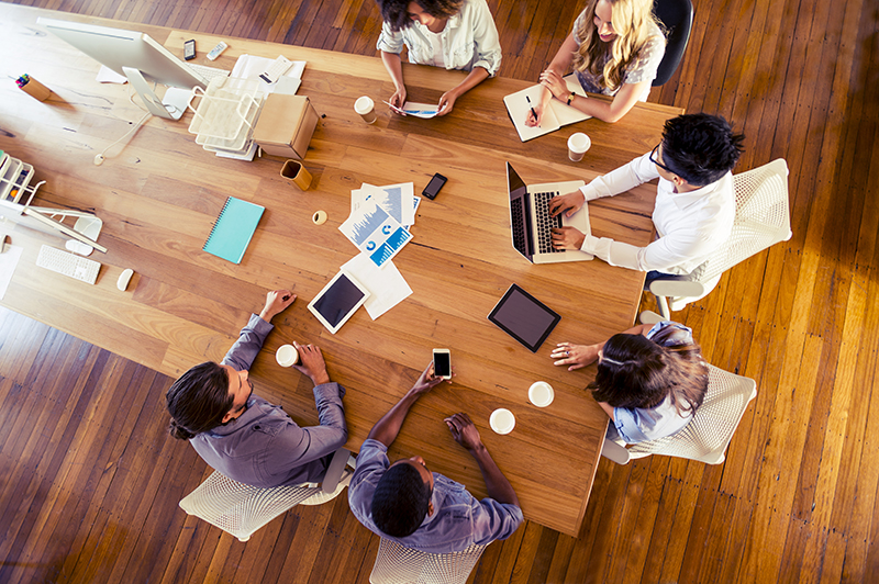 Aerial view of designers and engineers during a design meeting. The large wooden table around which they are seated contains sketches and notes as well as a series of laptops and mobile devices, such as tablets and smartphones.